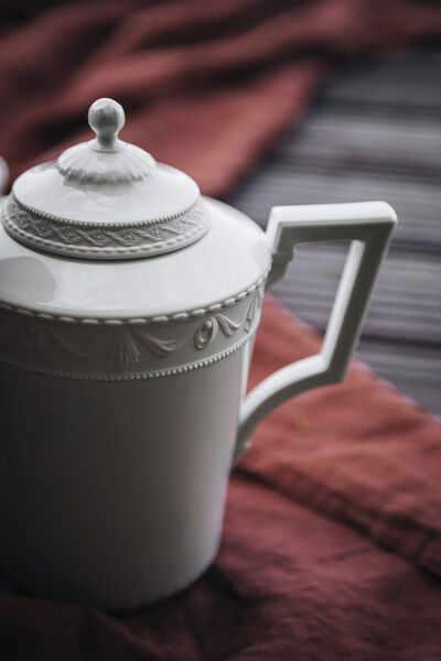 Close-up of a teapot from the KURLAND collection by KPM on a red picnic blanket on the jetty