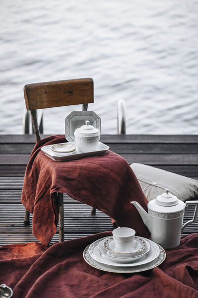 KPM tableware from the KURLAND series draped on a red picnic blanket on the jetty