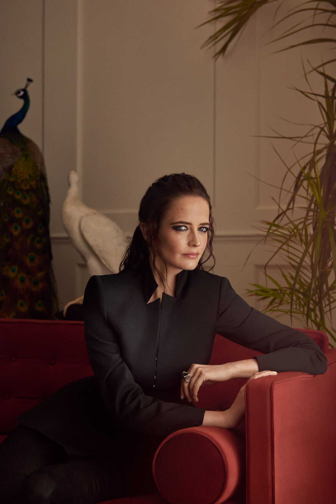 Eva Green wearing a black blouse siting on a red sofa