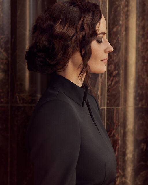 Lateral portrait of Eva Green with chignon and high-necked black blouse