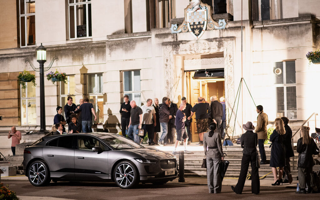 Grey Jaguar I-PACE stands surrounded by several people in front of building