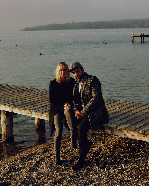 Franziska and Adnan Maral sitting on a wooden jetty at Ammersee