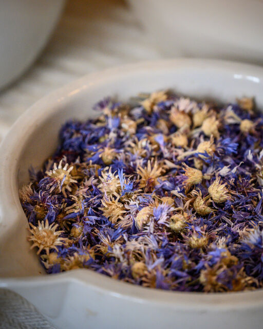 Close-up of dried blue flowers in white apothecary bowl