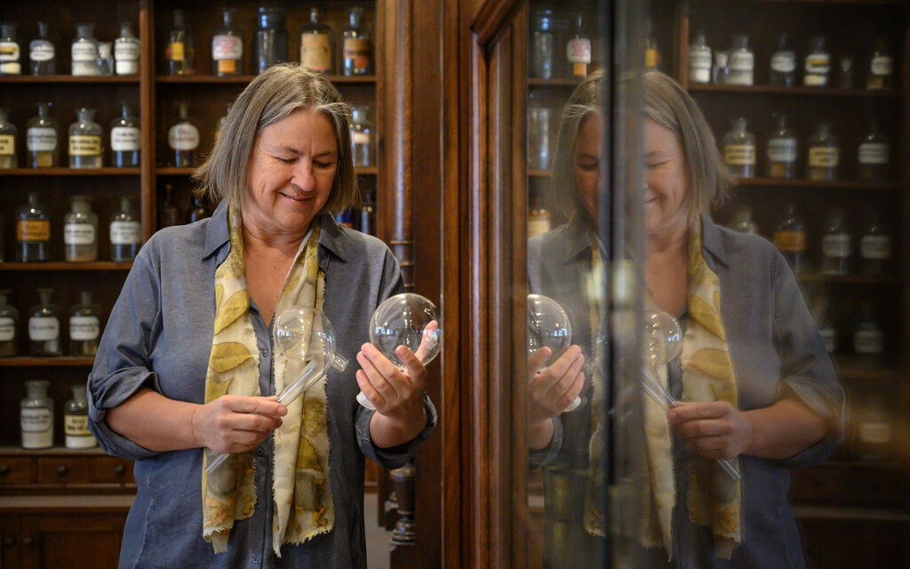 Martina Gebhardt stands in the pharmacy of the monastery Wessobrunn and looks at a jar with natural cosmetics