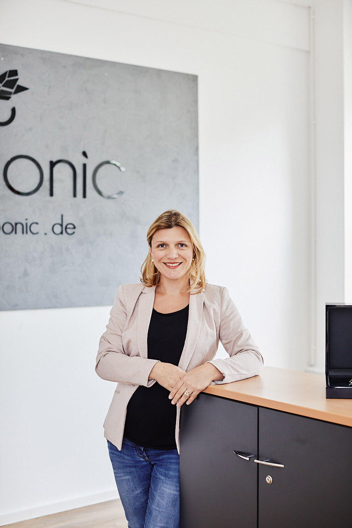 Sabine Linz, founder of amoonic.de, leans against a shelf in her office
