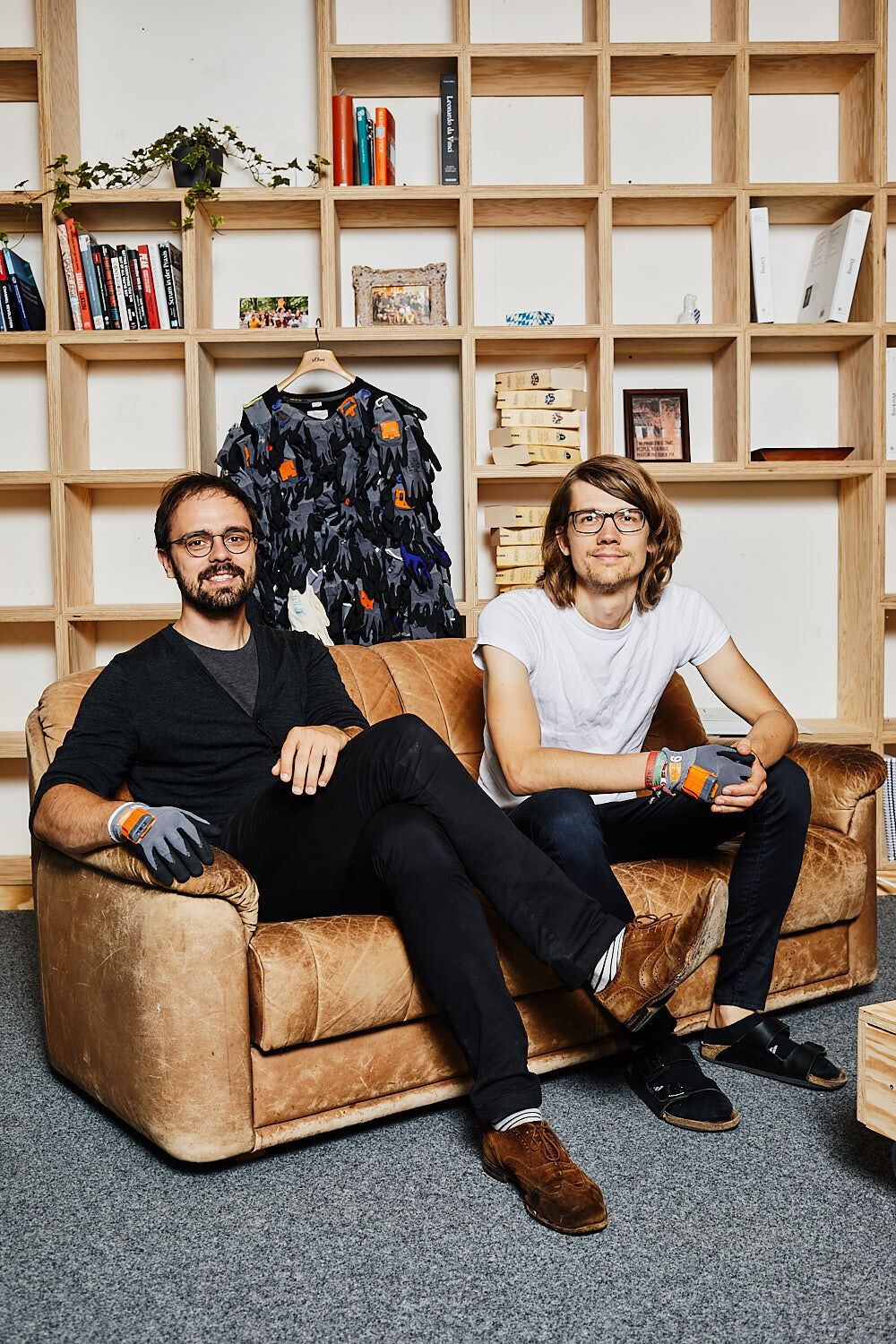 Thomas Kirchner and Paul Günther, founders of Proglove, sitting on a leather sofa in front of a bookshelf