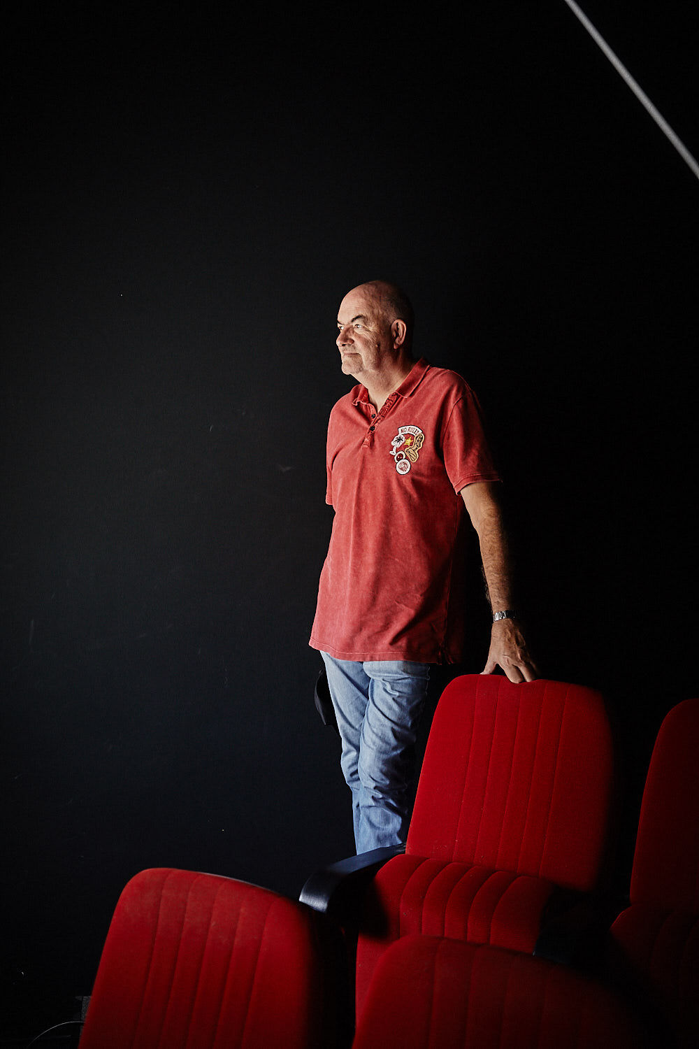 Thomas Zauner, founder of Scanline, leans against a red cinema chair in the cinema auditorium