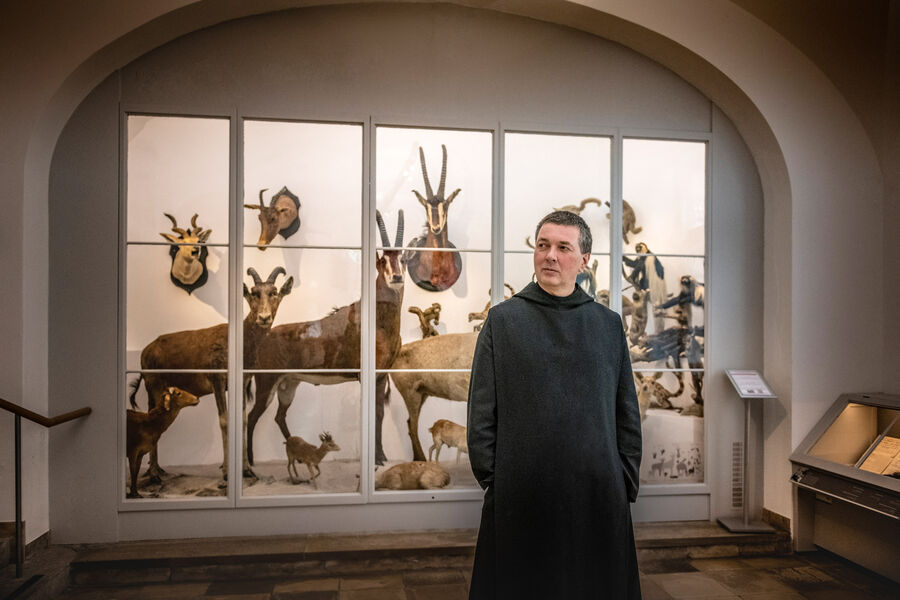 Monk of the Archabbey of Saint Ottilien stands in front of a showcase with stuffed mountain animals