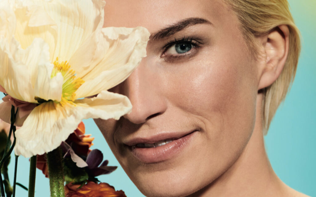 Close-up of a woman with natural make-up and several flowers in front of the right eye.