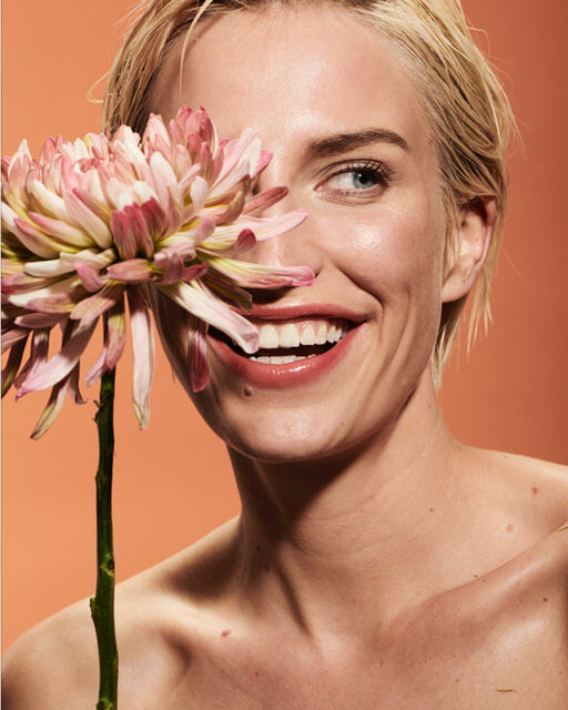 Close-up of a laughing woman with natural make-up and a blossom in front of her right eye.