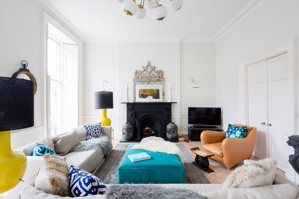 Living room with large sofa, colourful stools, apricot wing chair and fireplace