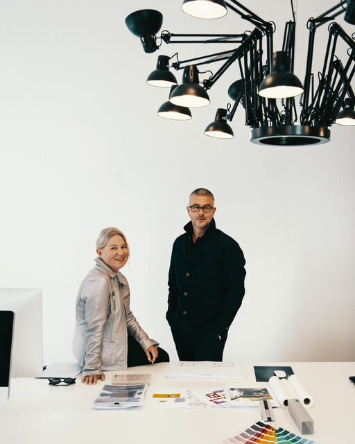 Ina and Gunther Laux at a large white desk in their architectural office