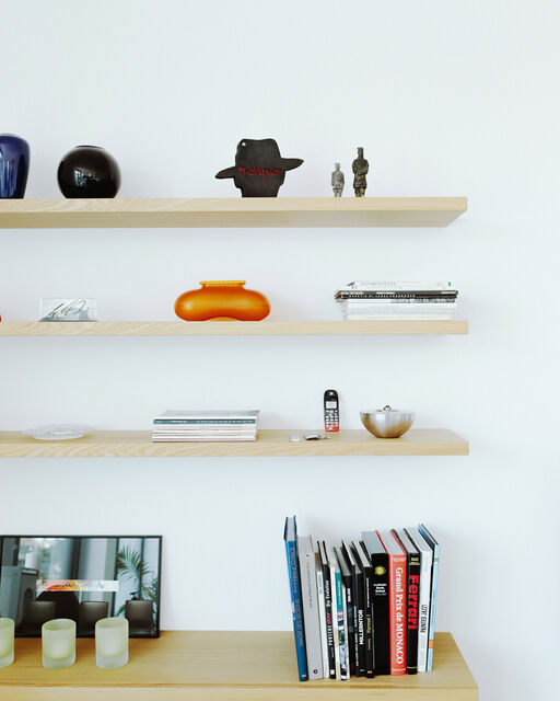 Three shelves with decoration hang on wall above chest of drawers with coffee table books