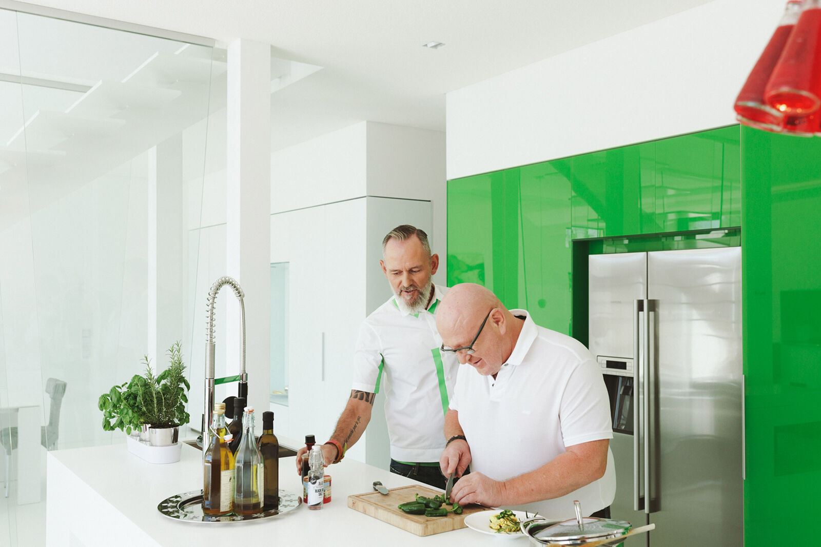 Two middle-aged men cooking in a modern kitchen with BORA extractor fan