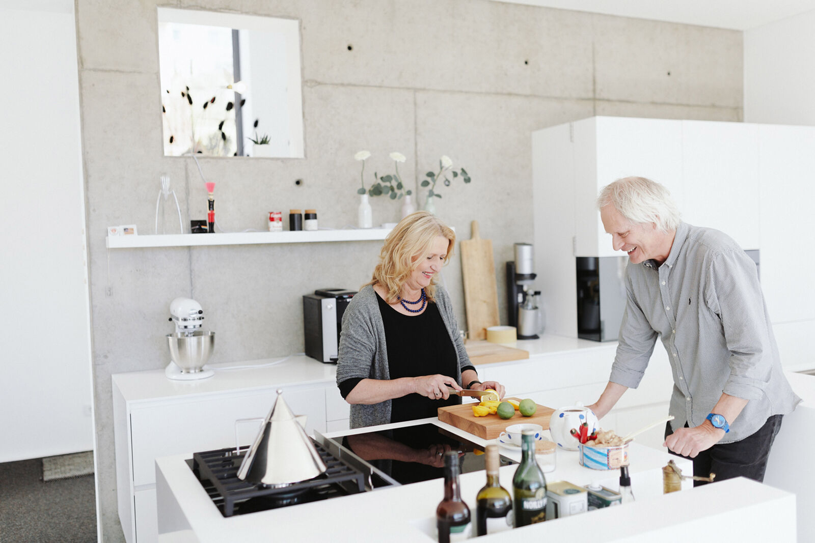Older couple cooks in open kitchen with BORA extractor system