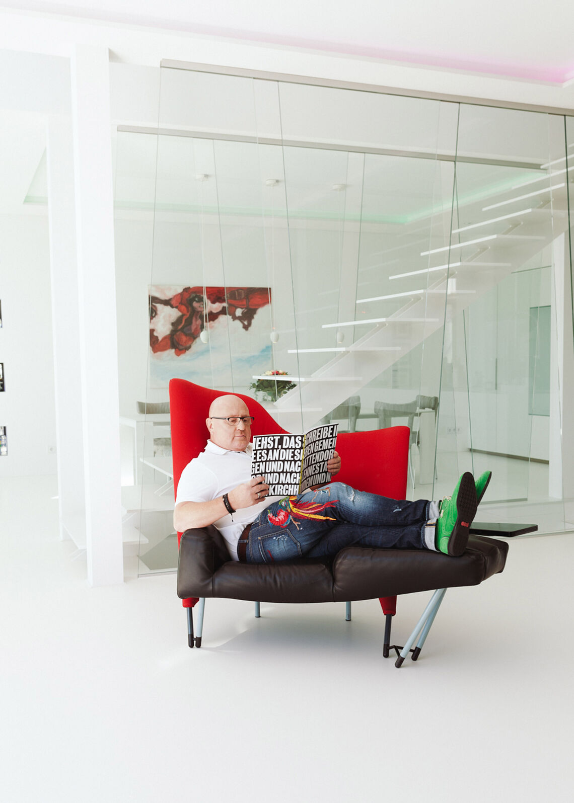 Bald man sitting on red-black armchair reading a magazine