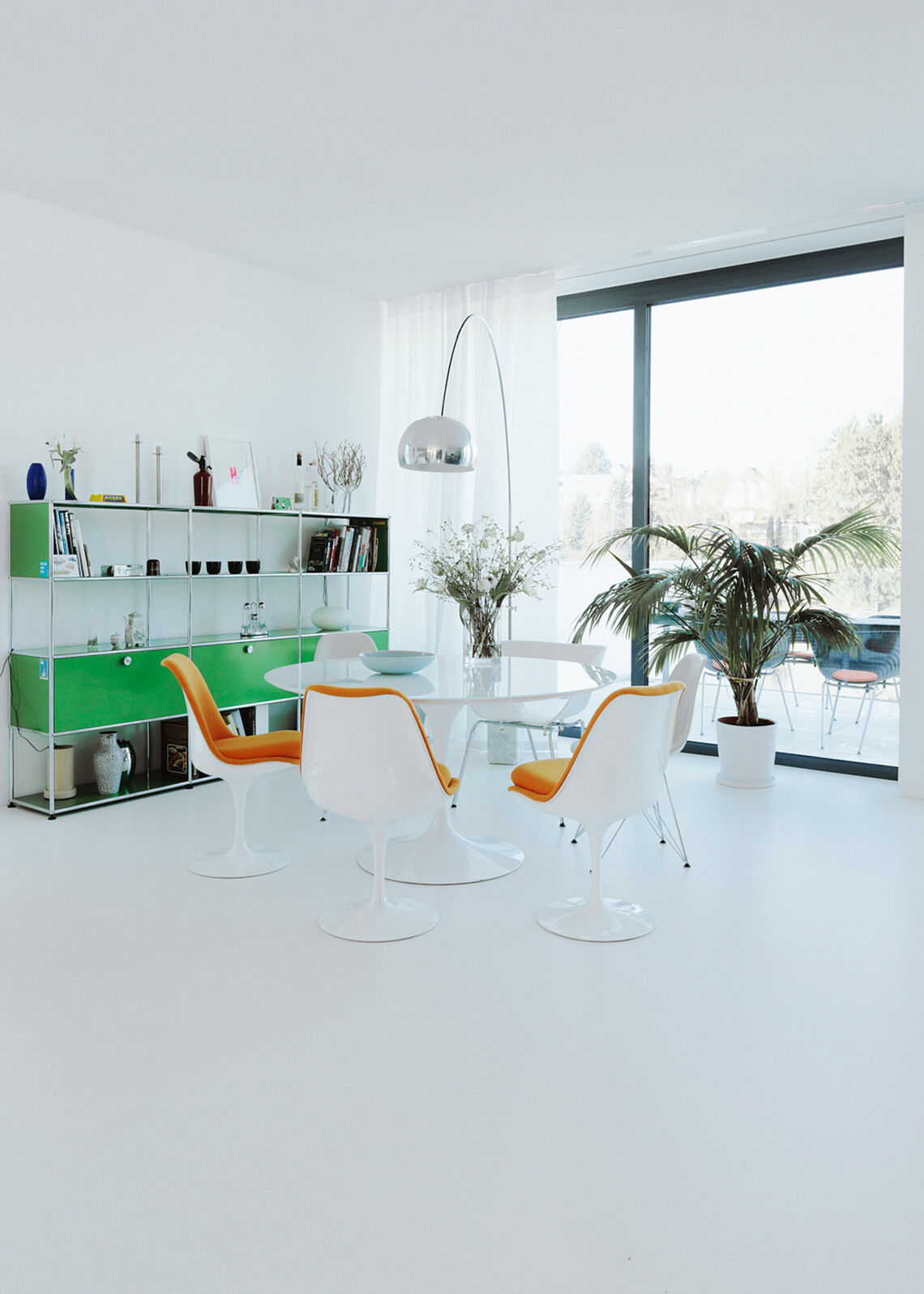 Open living/dining area with round dining table, orange chairs and green USM shelf