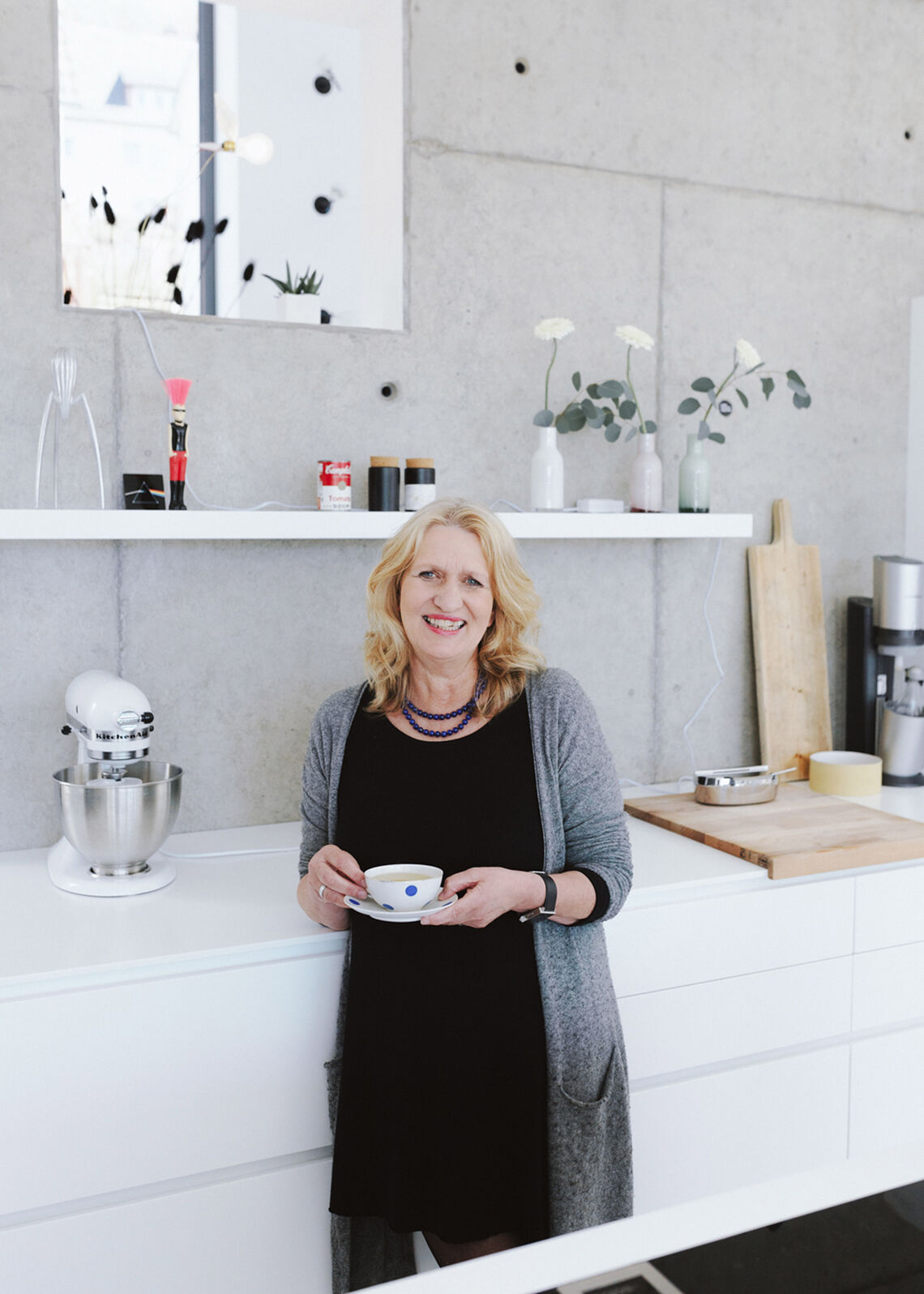 Middle-aged blonde woman stands in modern kitchen and holds a cup in her hand
