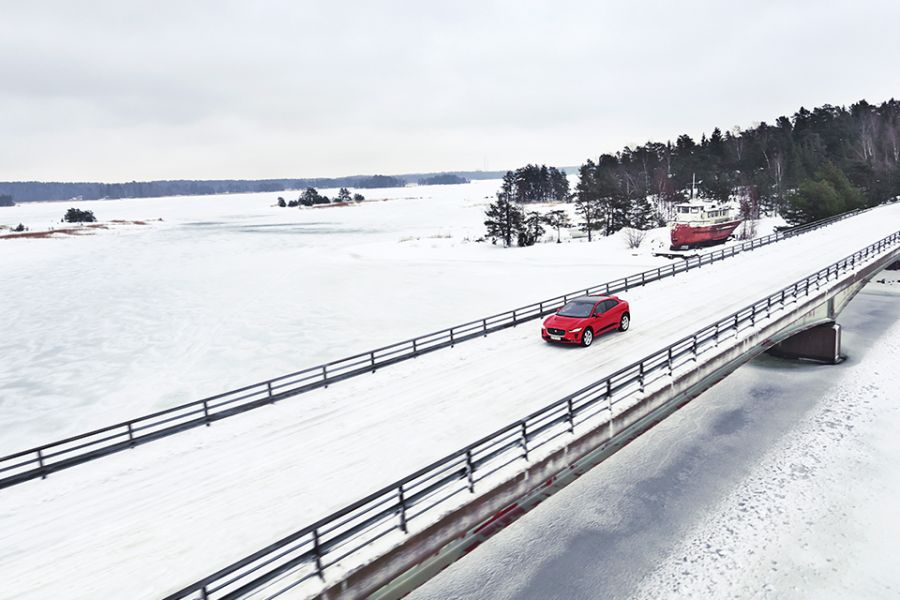 The Jaguar I-Pace drives on a snowy bridge over Finland's largest lake