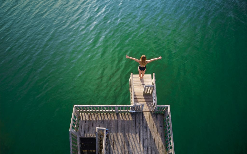 Iris Schmidbauer stands on a springboard with outstretched arms above the Ammersee in Utting
