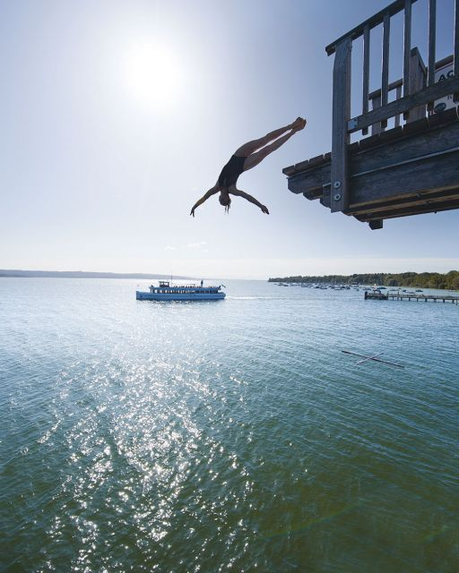 Iris Schmidbauer jumps from a tower in the background Ship on the Ammersee