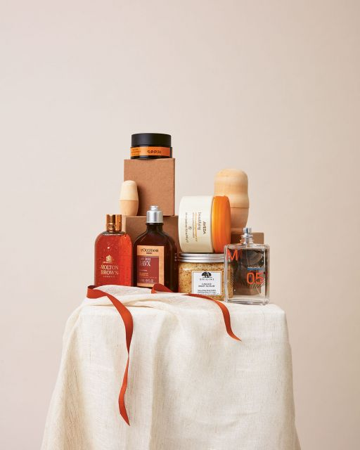 Still life with beige fabric, gift ribbon and beauty products against a beige background