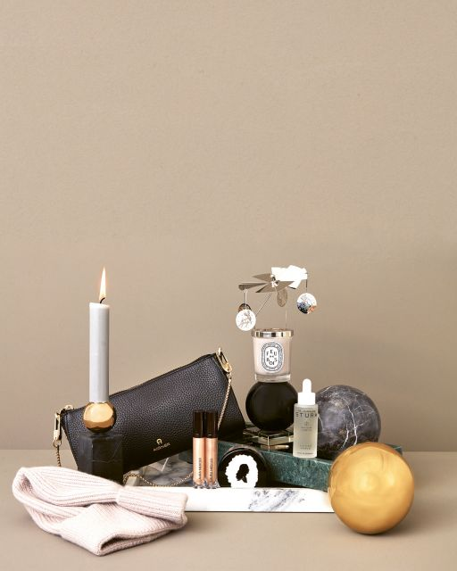 Still life with green and white marble tray, golden and grey ball, candle, beauty products and handbag