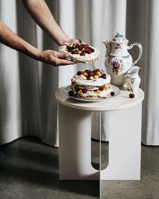 Man's arms are holding a fruit cake in front of small table with more cake and tea tableware