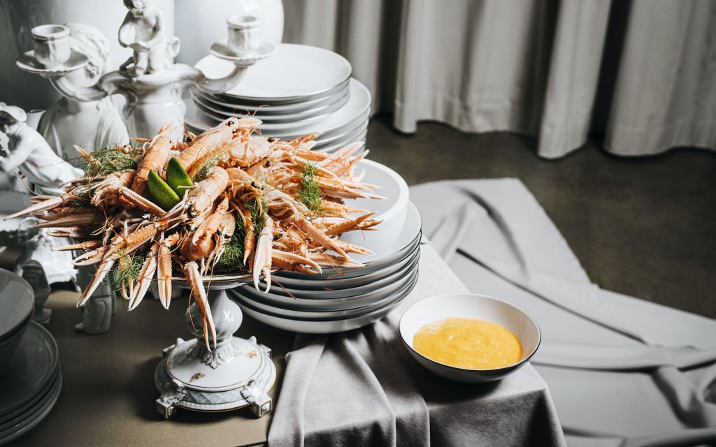 Cooked lobsters with yellow gravy arranged in front of white porcelain plates