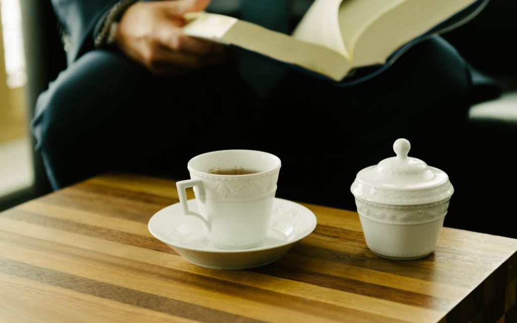 White sugar bowl and porcelain cup from KPM series Kurland stand on wooden table
